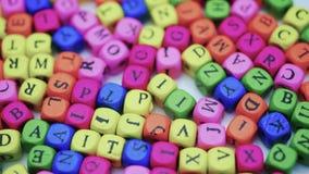 Letras en la tabla, letras coloreadas de giro en una tabla blanca metrajes