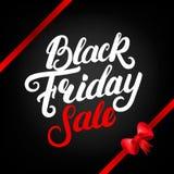 Letras escritas mano de la venta de Black Friday con la cinta y el arco rojos Imagen de archivo