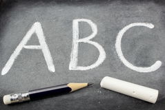 Letras, giz e lápis do ABC no quadro-negro Imagens de Stock