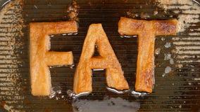 Letras grandes del FAT en una cacerola de asado a la parilla caliente en aceite fotos de archivo libres de regalías