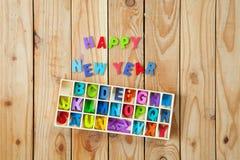 Letras inglesas coloridas nas caixas de madeira para o wordin da decoração Imagens de Stock Royalty Free