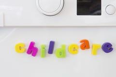 Letras magnéticas na máquina de lavar que soletra a puericultura Imagem de Stock Royalty Free