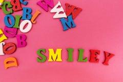 Letras multicoloras dispersadas en un fondo rosado, la palabra fotos de archivo libres de regalías