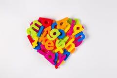 Letras plásticas brillantes en la forma de un corazón fotos de archivo libres de regalías