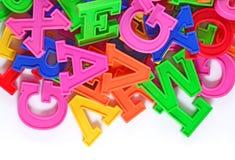 Letras plásticas coloridas del alfabeto en un blanco fotos de archivo