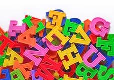 Letras plásticas coloridas del alfabeto en un blanco imagen de archivo