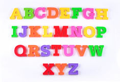 Letras plásticas coloridas del alfabeto en un blanco Fotografía de archivo