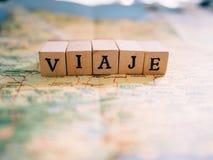 Letras que forman el viaje de la palabra en español encima de un mapa imagenes de archivo