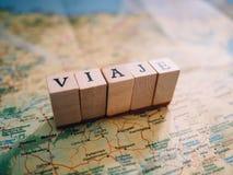 Letras que forman el viaje de la palabra en español encima de un mapa fotos de archivo libres de regalías