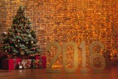 Letras '2016' y árbol de navidad adornado en fondo de la pared de ladrillo Fotos de archivo