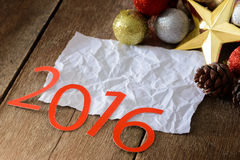 Letras 2016 y árbol de navidad adornado en la pared de madera Imagenes de archivo