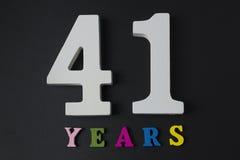 Letras y números cuarenta y uno años en un fondo negro Imágenes de archivo libres de regalías