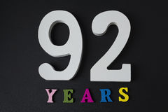 Letras y números noventa y dos años en un fondo negro Imagen de archivo libre de regalías
