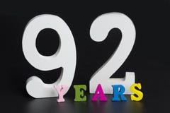 Letras y números noventa y dos años en un fondo negro Fotografía de archivo