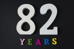 Letras y números ochenta y dos años, en un fondo negro Imagen de archivo libre de regalías