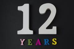 Letras y números por doce años en un fondo negro Imagenes de archivo