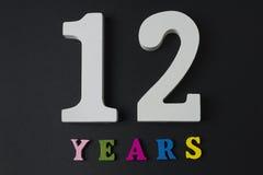 Letras y números por doce años en un fondo negro Fotografía de archivo libre de regalías