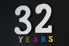 Letras y números treinta y dos en un fondo negro Imagen de archivo libre de regalías