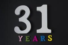 Letras y números treinta y uno años en un fondo negro Foto de archivo