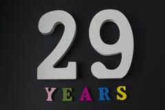 Letras y números veintinueve años en un fondo negro Fotos de archivo libres de regalías
