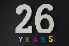 Letras y números veintiséis años en un fondo negro Foto de archivo libre de regalías