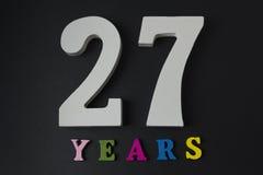 Letras y números veintisiete años en un fondo negro Imagen de archivo