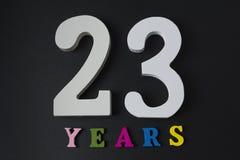 Letras y números veintitrés años en un fondo negro Foto de archivo libre de regalías