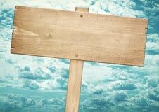 Letreiro de madeira marrom vazio contra o céu azul Foto de Stock