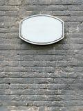 Letrero blanco oval en la fachada de una pared de ladrillo Imagen de archivo libre de regalías