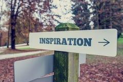 Letrero de la inspiración en posts de madera con un arr punteagudo correcto fotografía de archivo