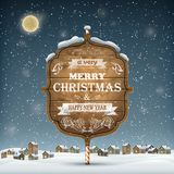Letrero de madera de la Navidad en la nieve Foto de archivo libre de regalías