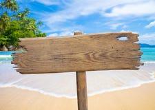 Letrero de madera viejo en la playa tropical Foto de archivo