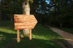 Letrero en blanco cerca de la trayectoria en bosque Imagen de archivo