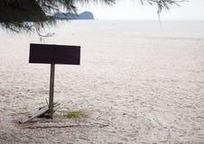 Letrero en blanco de la madera en la playa foto de archivo