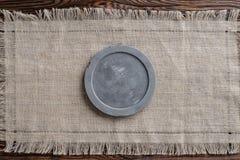 Letrero redondo concreto gris en tela ligera y fondo marrón de madera fotos de archivo