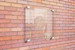 Letrero transparente en la pared de ladrillo roja Imagen de archivo libre de regalías