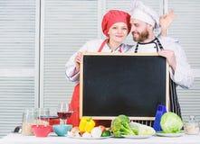Lets一起做晚餐 厨师和打手势好标志的厨房帮手在黑板 人和女孩夫妇主要类的 免版税库存图片