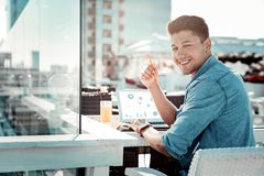 Clever brunette male working with computer. Lets analyze. Positive delighted man keeping smile on his face and turning head while sitting in semi position Stock Photos