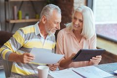Cheerful loving aged couple involved in paperwork at home Royalty Free Stock Photo