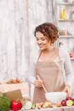 Lets cook something new and tasty. Beautiful young woman is cooking salad in the kitchen. She is reading a recipe from a book and smiling. The lady is standing Stock Images