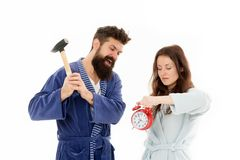 Lets get rid of this annoying alarm clock. Couple in bathrobes going to destroy alarm clock and stay at home. Breaking. Rules. Tired of early awakening. Man stock photo