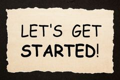 Let`s Get Started. Text on old torn paper on black background royalty free stock image