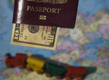Lets Go. A passport, some dollars, a map of countries and a toy train.  This is the dream of international travel and adventure Royalty Free Stock Images