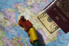 Lets Go. A passport, some dollars, a map of countries and a toy train.  This is the dream of international travel and adventure Royalty Free Stock Photography
