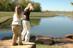 Lets go See the Pond. Two beautiful little blond sisters play and explore a nature area in a park. Spending time with family and being together. Older sister Stock Images