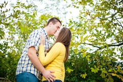 Lets Kiss!. A young men and women happily kissing in an outdoor wilderness setting wearing bright blue and yellow casual clothing holding yellow flowers Royalty Free Stock Image