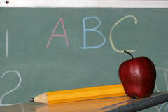 Lets learn. Chalk board pencil and apple on desk Stock Photography