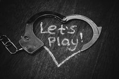 Lets play bdsm. Handcuffs for role-playing. Adult game concept. Handcuffs like heart with caption on black background. Royalty Free Stock Photo