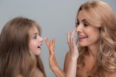 Delightful woman and little girl are testing new lotion royalty free stock image