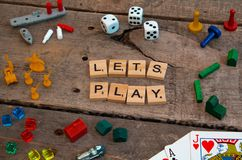 `Lets Play` made from Scrabble game letters. Risk, Battleship pieces, Monopoly, Settler of Catan and other game pieces royalty free stock images